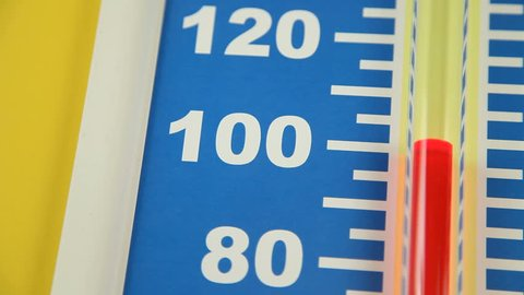 Close up of a Fahrenheit thermometer showing a rapid rise in temperature in the range of 80 to 120 degrees.