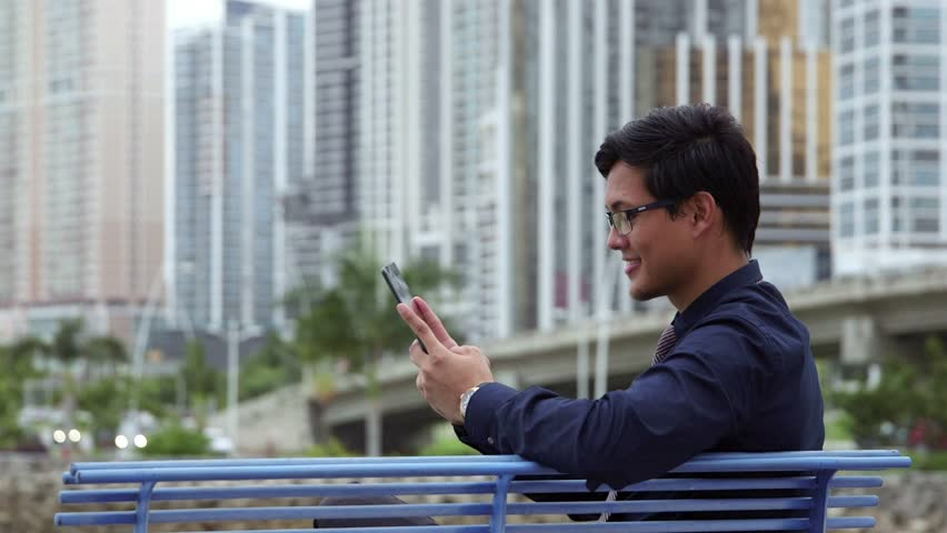 Portrait of chinese businessman sitting on bench in city park, near office buildings in Panama, and using ipad digital tablet for internet and email. People, career, asian man, pc, computer. 9of10 | Shutterstock HD Video #7412200