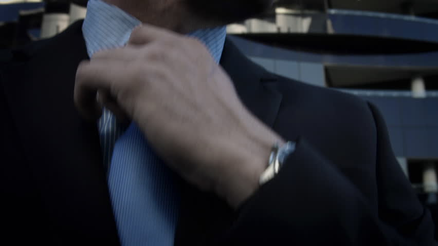 Suits business man fixing his tie before a deal in the city. Steadicam shot.    Shutterstock HD Video #7414210