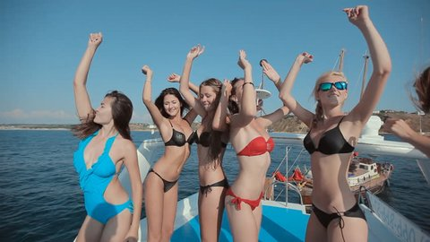 Girl in bikini on a yacht with the Russian flag and the red sails having fun, laughing and dancing