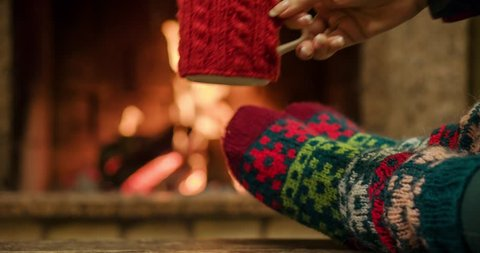Woman relaxes by warm fire with a cup of hot drink and wriggles her toes in woollen socks.  Close up on feet. Winter concept. Slow motion 120 fps. Dolly shot. 4k graded from RAW.