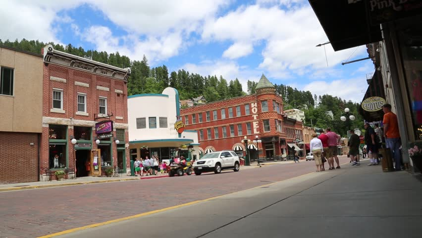 Deadwood, South Dakota, July 2014: A driver on a street legal ATV pulls up to a shop as tourists walk by on the Main Street of Deadwood, South Dakota, July 2014.