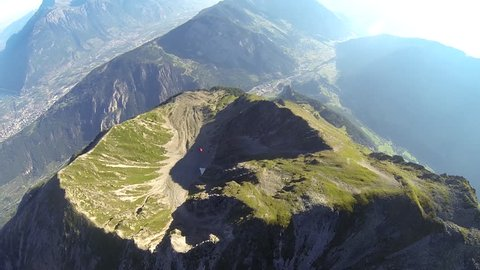 A base jumper in a wingsuit gliding down over a green mountain landscape, POV