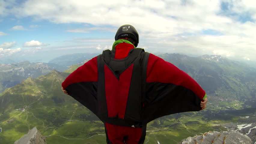 A base jumper in a wingsuit jumps from a cliff, gliding down over a green landscape