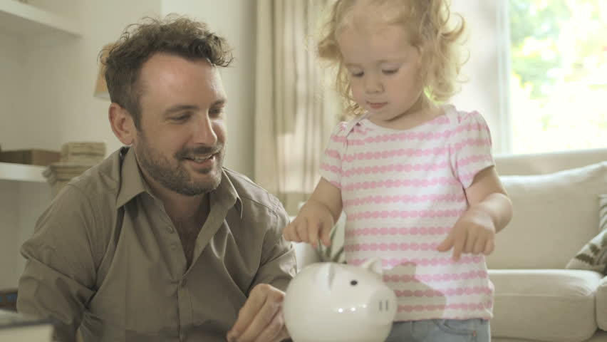 Father helping daughter to save money in piggy bank