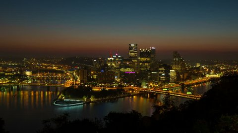(Time-lapse/Zoom-in) Morning twilight transitions to sunrise over Pittsburgh, Pennsylvania including the skyline, bridges and Point State Park at the confluence of the Allegheny and Monongahela Rivers