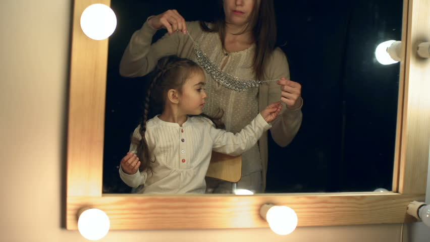 Mother fitting necklace to her daughter in front of the lighted make up mirror in the dark room