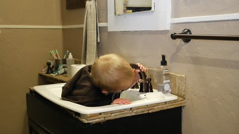 Cute blonde kid playing and drinking water in the bathroom sink. Smiling and waving to the camera
