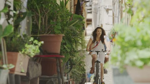 Attractive couple cycling in Italian city and having fun