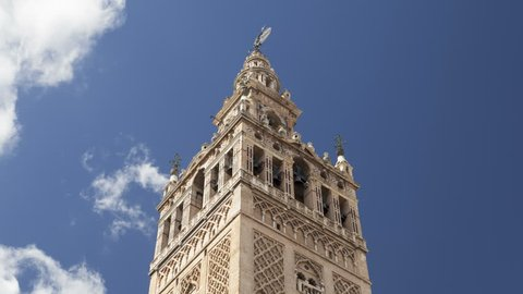 Timelapse of the Giralda Tower with blue sky and clouds passing behind. The Giralda Tower is in Seville, Andalusia, Spain. 4K, UHD, ultra HD resolution.