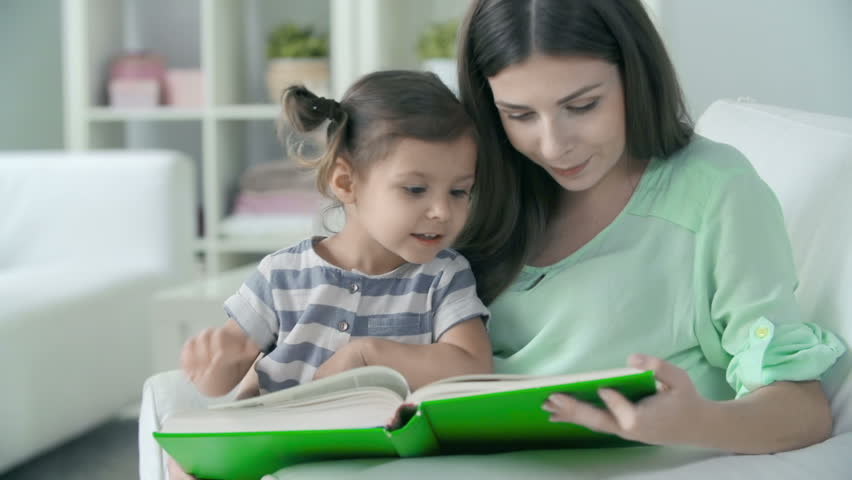 Close up of mother reading to her little daughter