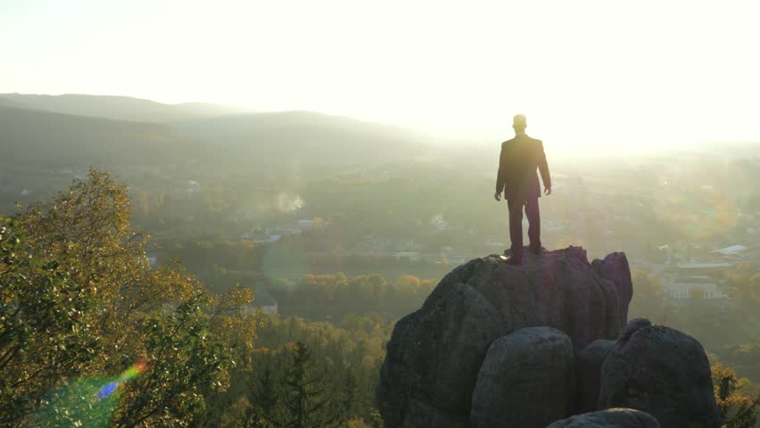 Office worker standing on a lonely rock | Shutterstock HD Video #7638490