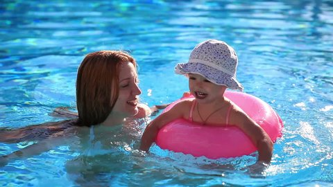 Mother and young daughter swimming in the pool with pink lifeline.