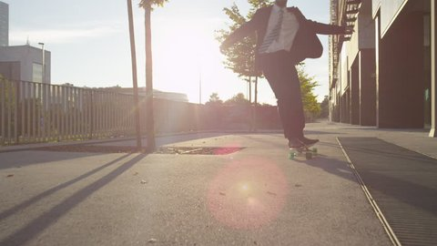 SLOW MOTION: Cool young businessman longboarding to work. Cheerful businessman with arms raised celebrating while skating along the downtown street. Ecstatic businessman skateboarding at golden sunset