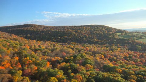 Sweeping fall aerial view New England. Near Berkshires, fall tree colors and fields sparkle in early morning light. 4k UHD aerial.