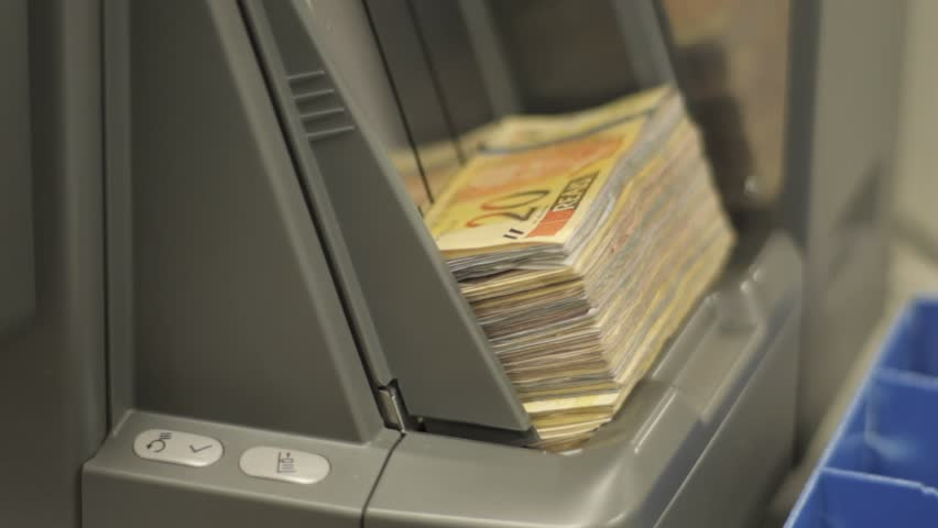 Operator placing Brazilian currency bank notes in to the input tray of a money counting machine | Shutterstock HD Video #7672000