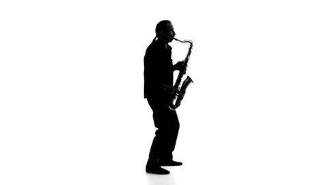 Dark silhouette of a musician who plays the saxophone on a white background