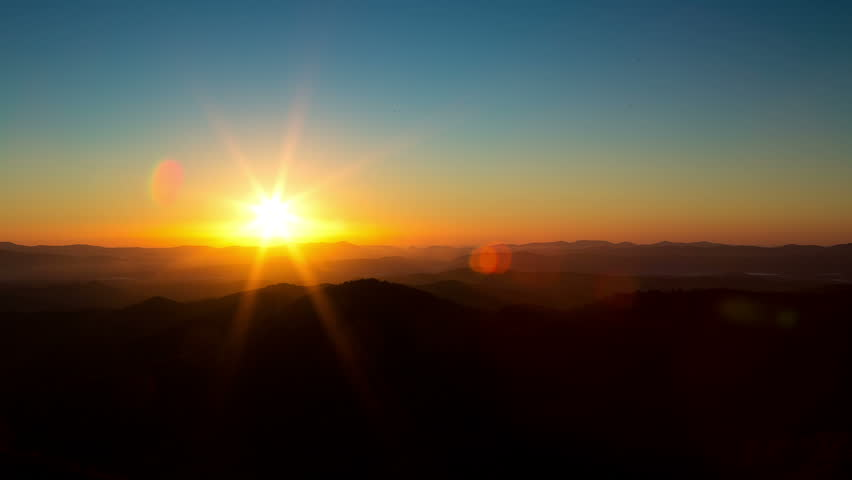 Time lapse of the sun rising from behind mountains. A beautiful lens flare moves through frame.