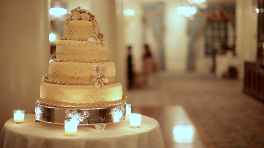 A golden wedding cake at left shot with shallow depth of field at a wedding in Boston