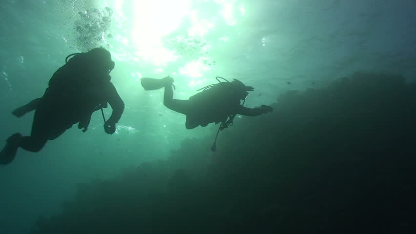 Two scuba divers swim past camera silhoutted by the Sun