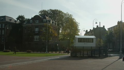 Wide shot of the US Consulate and police booth in Amsterdam. Someone runs towards the booth.
