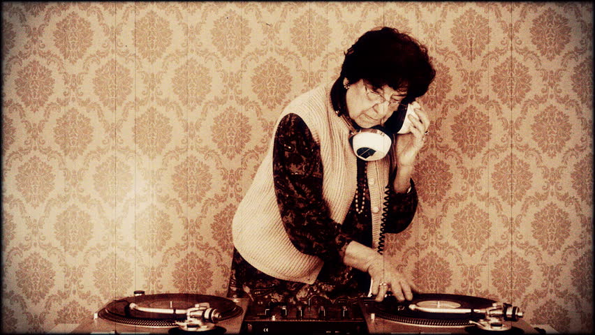 a very funky elderly lady dj, spinning records!! with aged film look