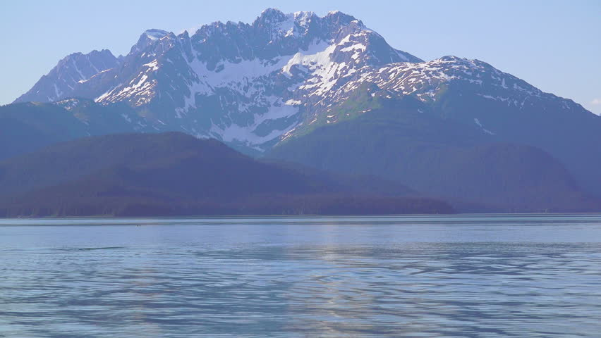 Epic and beautiful scene shot on a calm day in Alaska's Inside Passage waters with scenic mountain forming the backdrop as a humpback whale surfaces and spouts before gliding under the water.