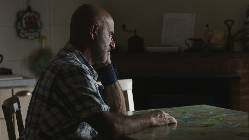 Desperate lonely man: sad man sitting alone in the kitchen | Shutterstock HD Video #7871380