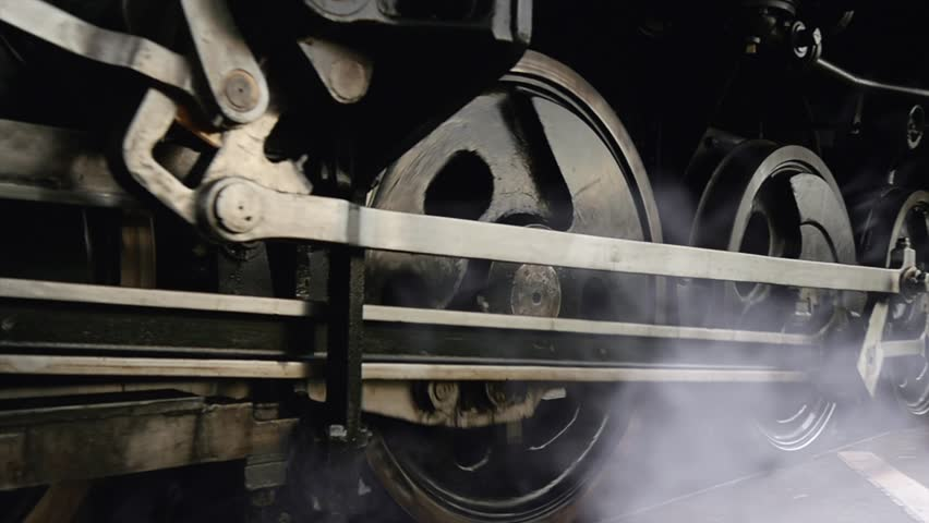 Steam engine train wheels passing in slow motion. historical technology background