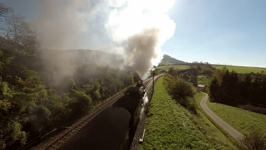 Flying over steam train at sunshine. old locomotive. heavy steam smoke background