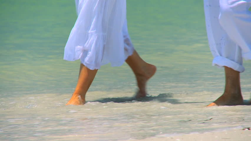Legs & feet of senior couple walking barefoot through the shallows on the beach 60FPS