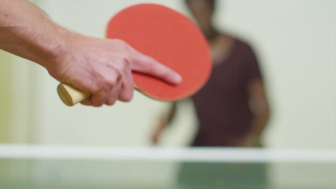 Slow motion close up shot of a man serving in table tennis as a small rally begins, shot on RED EPIC