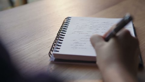 Close up of a woman writer hand writing in a notebook at home in the kitchen. RAW video record.