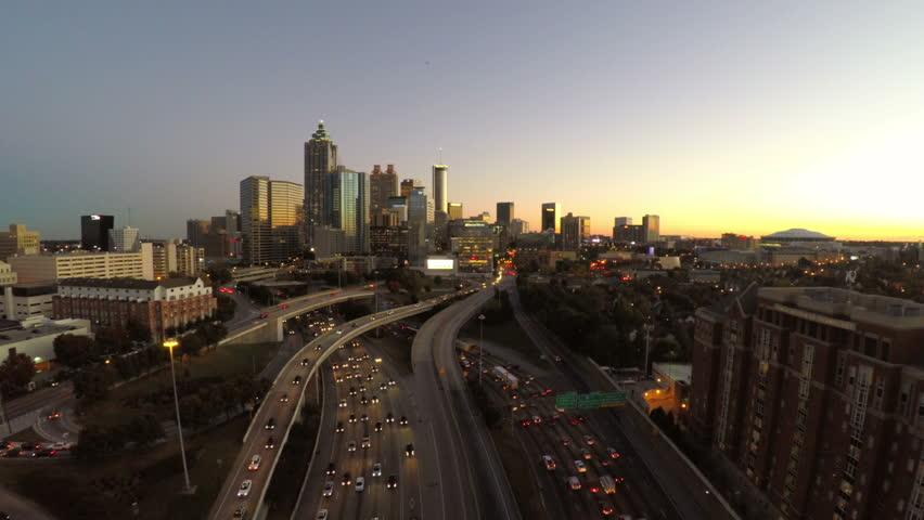 Atlanta cityscape aerial flying over freeway during dusk.