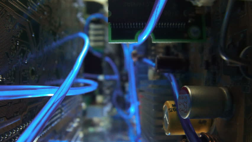 Computer system unit inside. Passage through the technical device, movement between the boards with glowing light guides. Dolly shot. Shallow depth of field