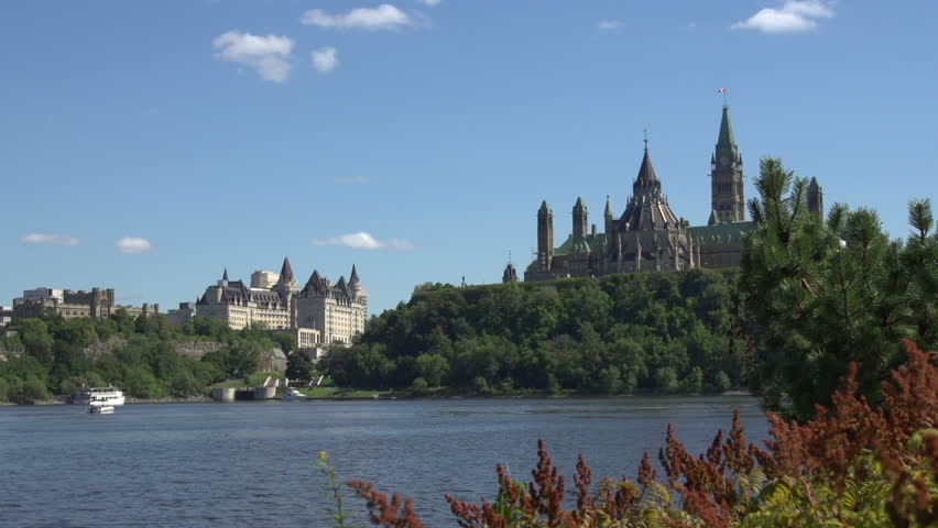 A mid-shot, pan left, of the city of Ottawa, Canada, with the rear view of the Parliament Building in the background and the Ottawa River in the foreground.