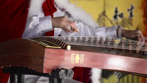 A woman in traditional costume playing guzheng.Guzheng is an traditional Chinese musical instrument,It belongs to the zither family of string instruments.