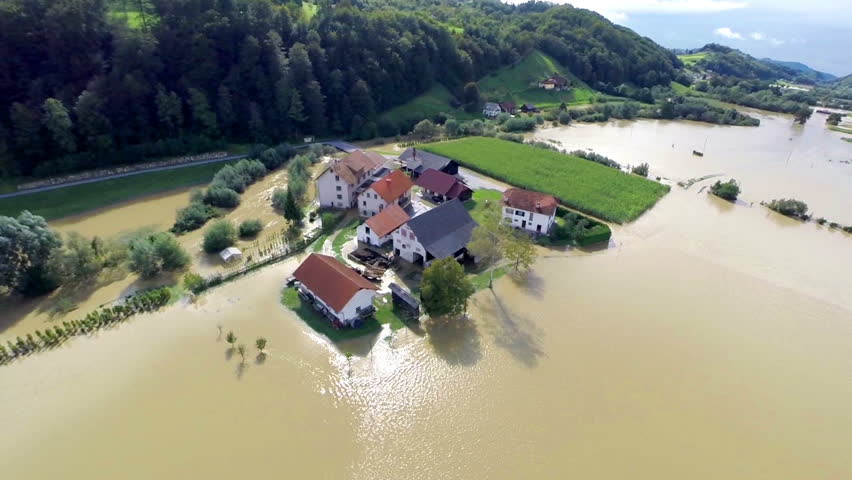 Home buildings in flood water with sun shining. Heavy flood after extensive river rise because of rainstorm. Bad protection against floods.