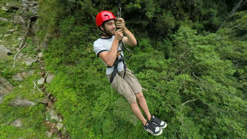 Young man sliding on zip line , camera rotates 360 degrees and track the subject , slow motion 120fps