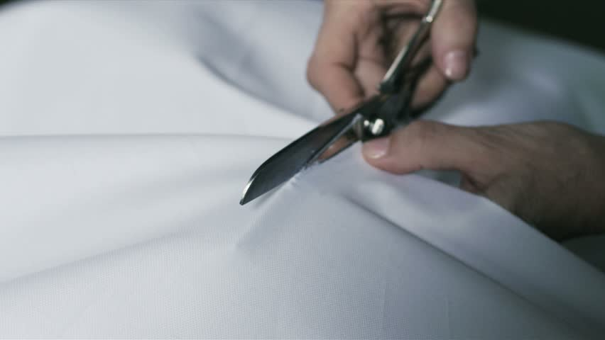 Super slow motion of middle-age woman hands with scissors cutting white fabric on a tabletop