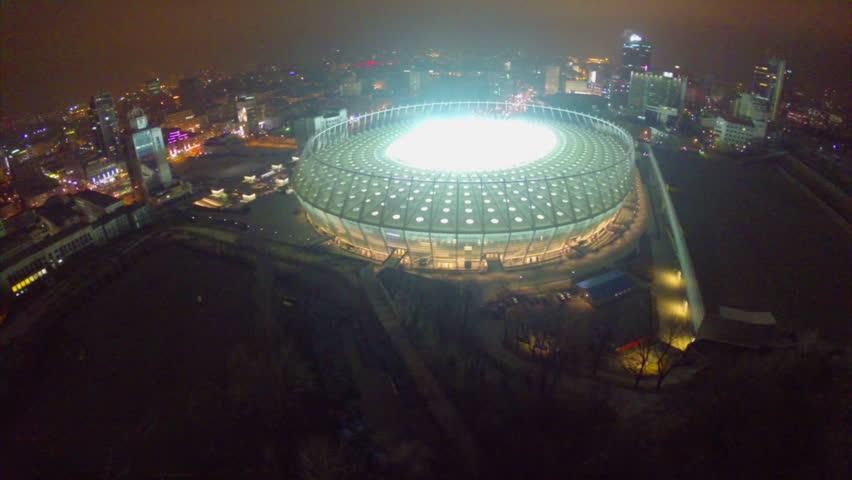 KIEV, UKRAINE - NOVEMBER 18, 2014 - Teams playing footbal on Olympiyskiy stadium. Beautiful view of stadium lights at night, city aerial, panorama