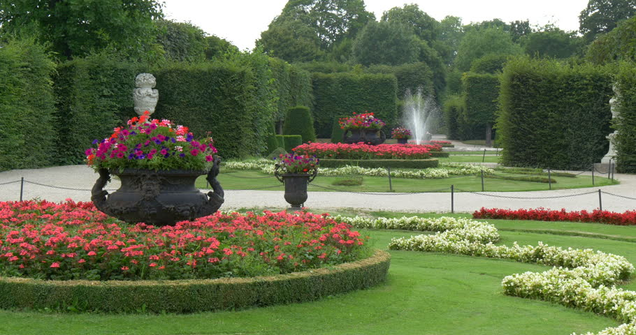 Green garden landscape design with trees, grass, flowers and water fountains, summer nature outdoor background, travel to the beautiful Schonbrunn Palace park in Vienna city, Austria, Europe
