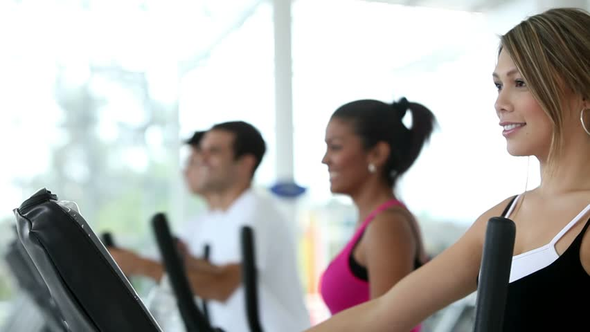 people at the gym exercising on a cross trainer