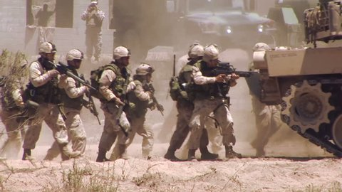 CAMP PENDLETON CALIFORNIA, JUNE 2013, US Marine soldiers attack. They save themselves behind a M1A1 Abrams tank.