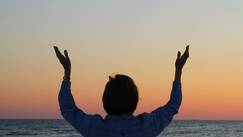Mature woman raises her hands while praying at the seashore.