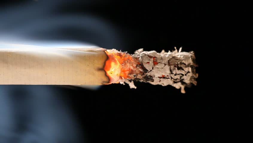 Macro view of burning cigarette with smoke on black