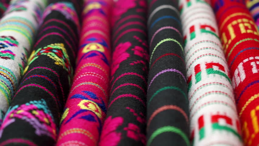 Dolly shot with short depth of field across authentic traditional Mexican ethnic design inspired colorful fabrics.