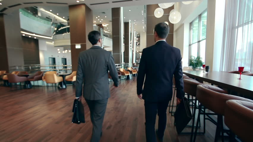 Camera following two businessmen walking along hotel lobby and discussing issues