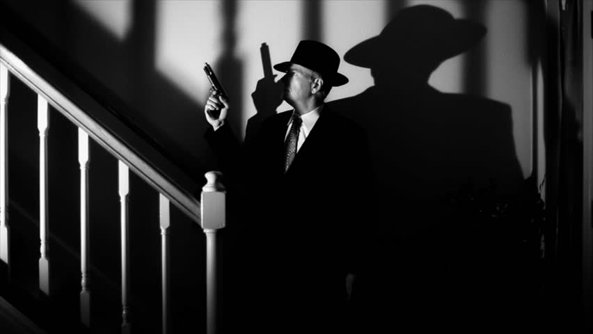 Deep shadows surround a man with a gun slowly walking up a staircase.