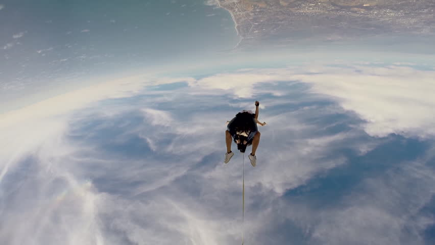 Two people doing tandem skydiving in the sky with a cityscape visible below, POV #8256670